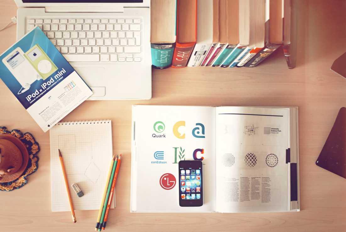 A logo designer's workspace including books, pencils, laptop, smartphone, and illustrations.