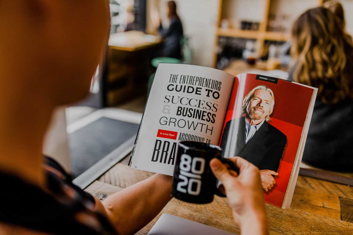 A man reading a book on how to launch an online business.
