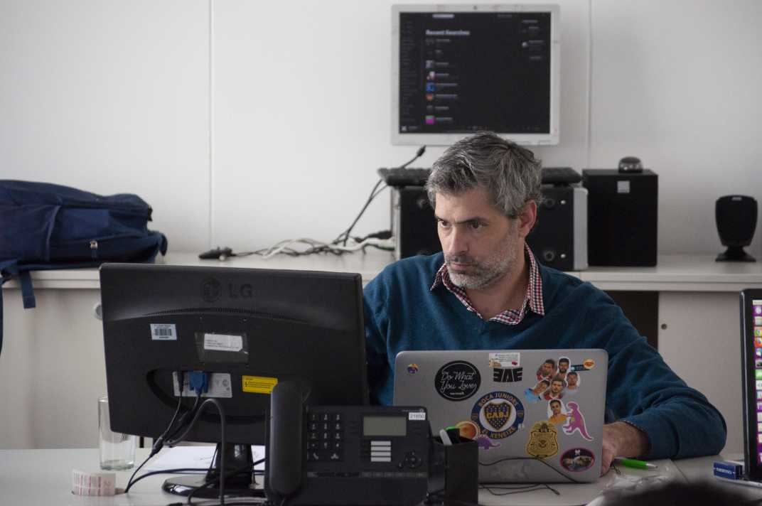 Man using different graphic design outsourcing tools in a laptop and monitors.