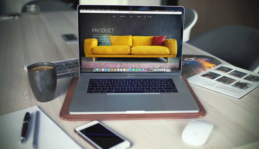 A website design shown in a laptop with smartphone, books, and coffe in the background.