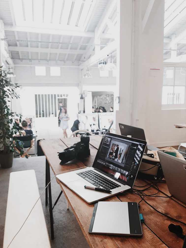 Laptops, tablet, and camera in the foregrgraphic in a white design studio.